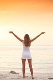 La donna gode del tramonto sopra il mare immagini stock