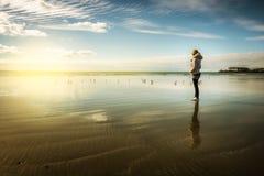 La donna gode del tramonto sulla spiaggia Fotografie Stock