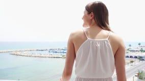 La donna gode della vista del mare dal terrazzo Condizione femminile sul balcone ed esaminare porticciolo al rallentatore archivi video