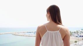 La donna gode della vista del mare dal terrazzo La femmina esce sul balcone al rallentatore ed esamina il porticciolo stock footage