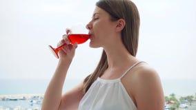 La donna gode della vista del mare dal terrazzo Femmina sul vino rosato della bevanda di vacanza sul balcone al rallentatore archivi video