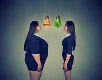 La donna grassa che esamina felice dimagrisce la ragazza adatta Concetto di scelta di dieta immagini stock