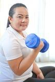 La donna grassa fa la forma fisica con la testa di legno Fotografia Stock