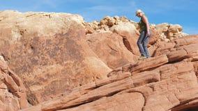 La donna grassa matura sportiva scende con attenzione le rocce rosse del canyon video d archivio