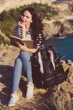 La donna graziosa è libro di lettura sul picco della roccia Fotografia Stock