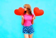 La donna graziosa bacia un pallone rosso sotto forma di cuore sul blu Fotografia Stock