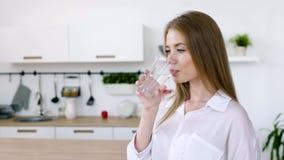 La donna graziosa beve l'acqua da una tazza di vetro di mattina stock footage