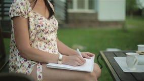 La donna graziosa in camicia da notte gira la pagina del taccuino e scrive una lettera sulle sue ginocchia archivi video