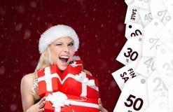 La donna graziosa in cappuccio di Natale tiene un insieme dei presente dalla vendita Fotografia Stock