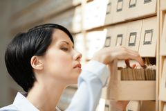 La donna graziosa cerca qualcosa nel catalogo di scheda Fotografia Stock Libera da Diritti