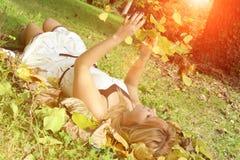 La donna graziosa che si trova sul prato con la caduta copre di foglie in autunno Fotografie Stock