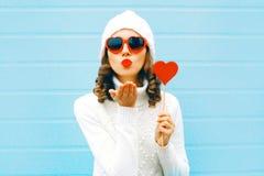 La donna graziosa del ritratto che soffia le labbra rosse invia il bacio dell'aria con la lecca-lecca immagine stock libera da diritti