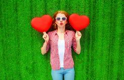 La donna graziosa del ritratto giudica il rosso aerostati sotto forma di cuore Fotografia Stock Libera da Diritti
