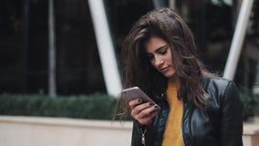 La donna graziosa della giovane donna in un bomber utilizza il suo telefono mentre sta nel centro urbano, guarda intorno Urbano video d archivio