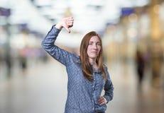 La donna graziosa di affari che fa il pollice giù gesture sopra il backgr della sfuocatura immagine stock