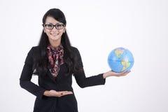 La donna graziosa di affari tiene un globo fotografie stock