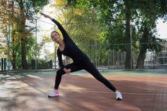 La donna graziosa di forma fisica fa l'allungamento degli esercizi durante il trai di sport Immagini Stock