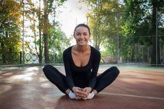 La donna graziosa di forma fisica fa l'allungamento degli esercizi durante l'allenamento sopra Fotografia Stock Libera da Diritti