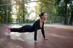 La donna graziosa di forma fisica fa l'allungamento degli esercizi durante la formazione della o Fotografia Stock