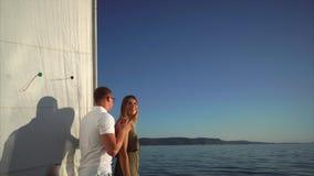 La donna graziosa e l'uomo bello stanno stando su un yacht, galleggiante nel mare video d archivio