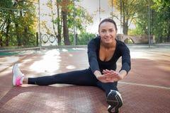 La donna graziosa fa l'allungamento degli esercizi durante il wor di addestramento di sport Immagini Stock