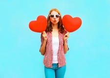 La donna graziosa fa un bacio dell'aria con i palloni rossi nella forma Fotografia Stock