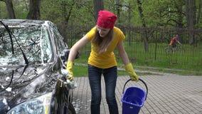 La donna graziosa lava la sua automobile con la spugna in aria aperta video d archivio