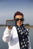 La donna graziosa mostra a telefono l'esposizione in bianco Immagine Stock