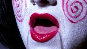 La donna graziosa nello stile di orrore compone canta una canzone su fondo scuro Immagine Stock