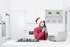 La donna graziosa porta il cappello di Santa nella cucina Fotografia Stock Libera da Diritti