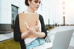 La donna graziosa scrive con la penna sul documento cartaceo e sulle informazioni di ricerca in Internet sul computer portatile n Immagine Stock Libera da Diritti