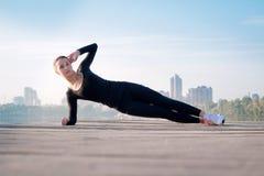 La donna graziosa si esercita sul pilastro durante l'allenamento di addestramento di sport Fotografie Stock Libere da Diritti