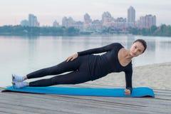 La donna graziosa si esercita sul pilastro durante l'allenamento di addestramento di sport sopra Fotografie Stock Libere da Diritti
