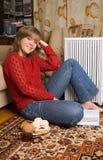 La donna graziosa si siede su una moquette Fotografia Stock Libera da Diritti