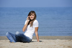 La donna graziosa si siede sulla sabbia con il cellulare Fotografia Stock