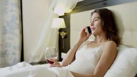 La donna graziosa si trova a letto e beve il vino rosso da vetro mentre parla sopra lo smartphone stock footage