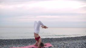 La donna graziosa sta facendo il headstand sulla spiaggia della ghiaia del mare stock footage