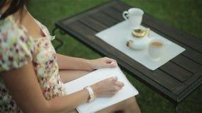 La donna graziosa in una camicia da notte ha prima colazione fuori e scrive una lettera sulla carta sul suo rivestimento stock footage