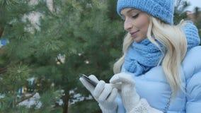 La donna graziosa in vestiti caldi utilizza un telefono vicino all'abete stock footage