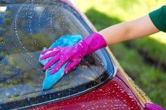 La donna in guanti di gomma lava un'automobile rossa Detersivo di pulizia immagine stock libera da diritti