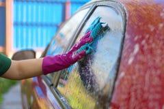 La donna in guanti di gomma lava un'automobile rossa Detersivo di pulizia fotografia stock libera da diritti
