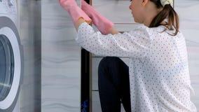 La donna in guanti di gomma rosa lava la mobilia dura della cucina con il panno Sedendosi sul pavimento Vista laterale archivi video