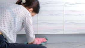 La donna in guanti di gomma rosa lava la mobilia dura della cucina con il panno Sedendosi sul pavimento Vista posteriore archivi video