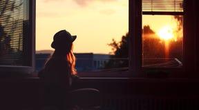 La donna guarda dalla finestra Immagini Stock Libere da Diritti