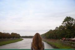 La donna guarda fuori sopra il paesaggio vago del fiume Fotografia Stock