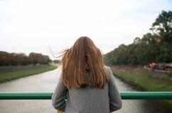 La donna guarda fuori sopra la vista vaga del fiume Immagine Stock