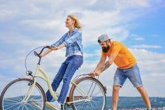 La donna guida il fondo del cielo della bicicletta Come imparare guidare bici come adulto Ragazza che cicla mentre il ragazzo la  fotografia stock