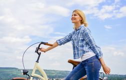 La donna guida il fondo del cielo della bicicletta Come imparare guidare bici come adulto Svago attivo Il più sano la maggior par fotografie stock