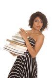 La donna ha barrato la pila del vestito di libri che sembrano seria Immagine Stock Libera da Diritti