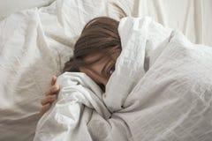 La donna ha coperto il suo fronte di cuscino. Esaminando macchina fotografica. Fotografie Stock Libere da Diritti
